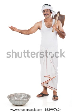 Portrait of a farmer carrying spade on his shoulders and gesturing - stock photo