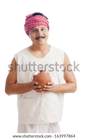 Portrait of a farmer holding a piggy bank and smiling - stock photo