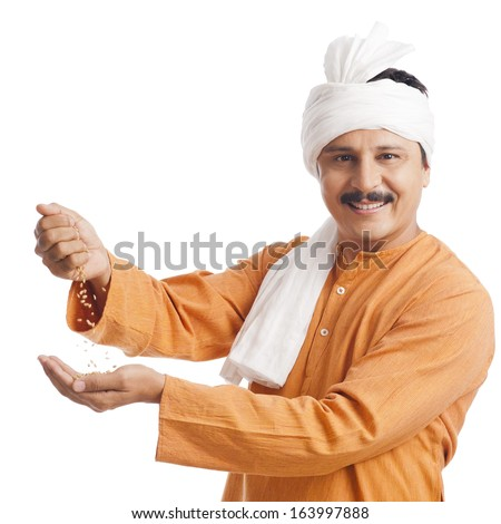Portrait of a farmer holding wheat in his hand and smiling - stock photo