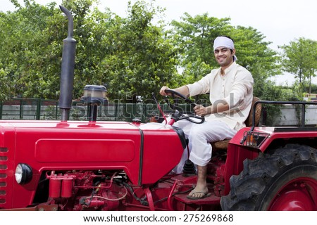 Portrait of a farmer sitting on a tractor smiling - stock photo
