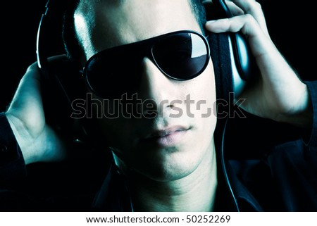 Portrait of a fashion guy listening music with headphones - stock photo