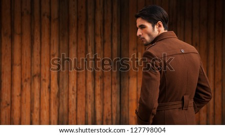portrait of a fashion model with copy space, man wearing over coat and standing the grunge wooden door. - stock photo