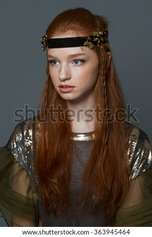 Portrait of a fashion redhead woman standing over gray background - stock photo