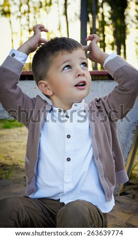 Portrait of a fashion 3 year old child. Handsome boy with hands over his head. Outdoor picture. - stock photo