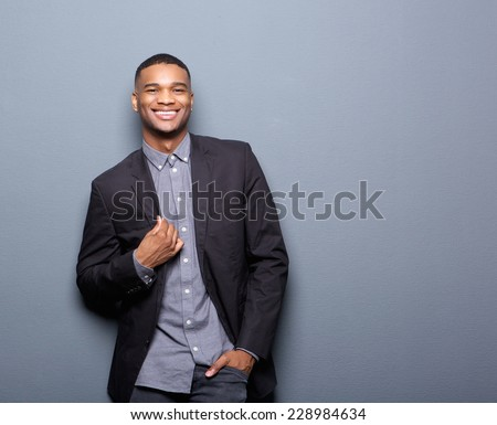 Portrait of a fashionable african american man smiling on gray background - stock photo