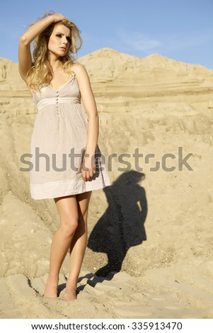 Portrait of a fashionable beautiful young adult attractive sexy and sensuality blonde woman in brown dress on the summer sunlight background desert - stock photo