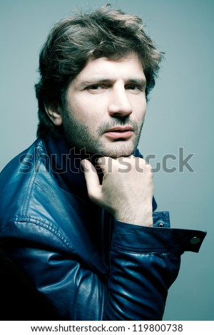 Portrait of a fashionable handsome man in blue jacket over light blue background holding his head. Studio shot - stock photo