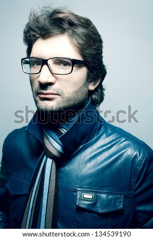 Portrait of a fashionable handsome man in blue jacket with striped scarf over light blue background. Copy-space. Studio shot - stock photo