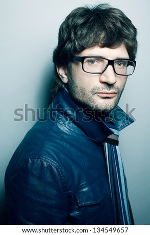 Portrait of a fashionable handsome man in blue jacket with striped scarf over light blue background. Urban style. Studio shot