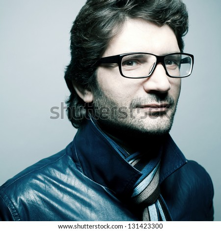 Portrait of a fashionable handsome man with a friendly smile in blue jacket with striped scarf posing over light blue background. Hipster (vogue) style. Perfect hair. Close up. Studio shot - stock photo