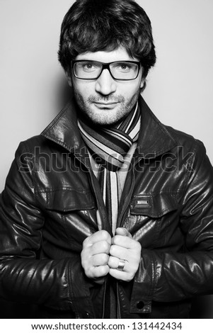 Portrait of a fashionable handsome man with a friendly smile in leather jacket with striped scarf posing over light gray background. Hipster (vogue) style. Perfect hair. Studio shot - stock photo