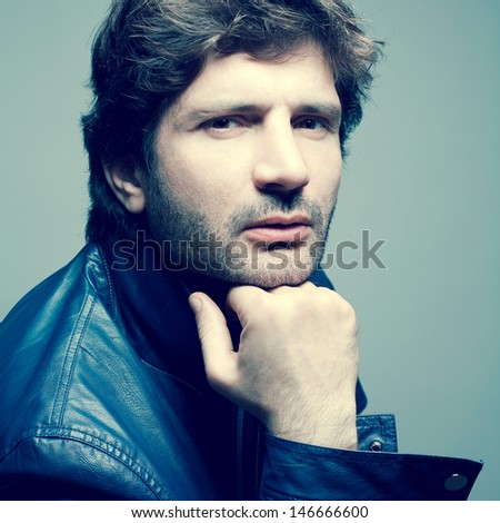 Portrait of a fashionable handsome mature man in blue leather jacket posing over light blue background and holding his head. Vogue style. Close up. Studio shot - stock photo