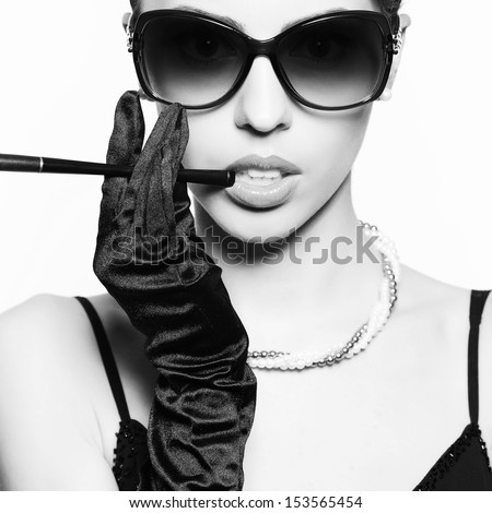 Portrait of a fashionable model in vintage sunglasses with a cigarette holder. Perfect skin. Great pearl accessories. Retro style. Close up. Black & white (monochrome) studio shot