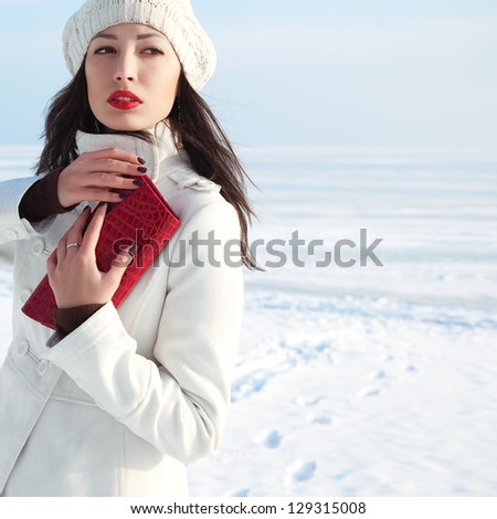 Portrait of a fashionable model in white coat and beret holding red leather clutch and posing at the winter seaside. Sunny weather. French style. Copy-space. Outdoor shot. - stock photo