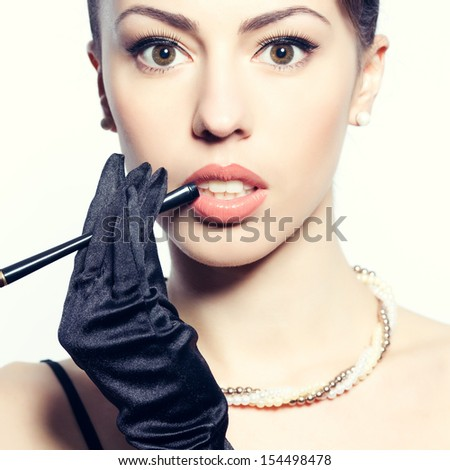 Portrait of a fashionable model with a cigarette holder. Perfect skin. Great pearl accessories. Retro (hollywood) style. Close up. Studio shot