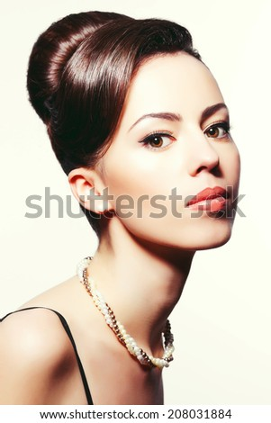 Portrait of a fashionable model with great hairdo and stylish make-up over white background. Perfect skin and glossy hair. Great pearl accessories. Audrey Hepburn style. Close up. Studio shot - stock photo