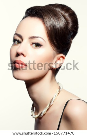 Portrait of a fashionable model with great hairdo and stylish make-up. Perfect skin and hair. Great pearl accessories. Retro style. Close up. Studio shot