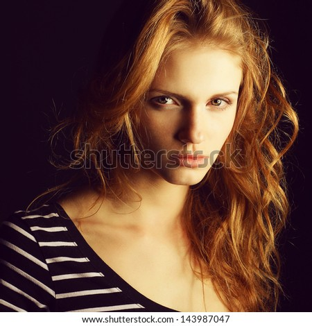 Portrait of a fashionable red-haired (ginger) model in t-shirt with black and white stripes posing over black background. Serious glance. Healthy skin & hair. Close up. Copy-space. Studio shot