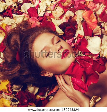 Portrait of a fashionable red-haired (ginger) model with sexy red lips lying on fading rose petals background. Studio shot - stock photo