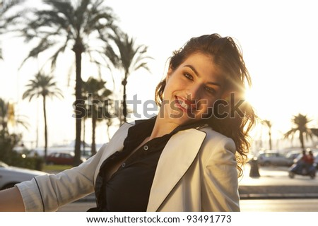 Portrait of a fashionable woman sitting outdoors, with sun rays filtering from the back. - stock photo