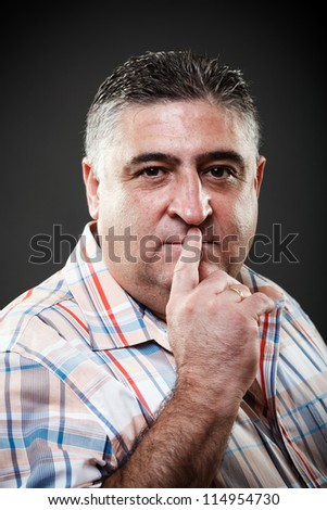 Portrait of a fat man making silence gesture on gray background - stock photo