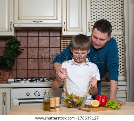 Portrait of a father and his son cooking in the kitchen. Healthy food - vegetable salad.