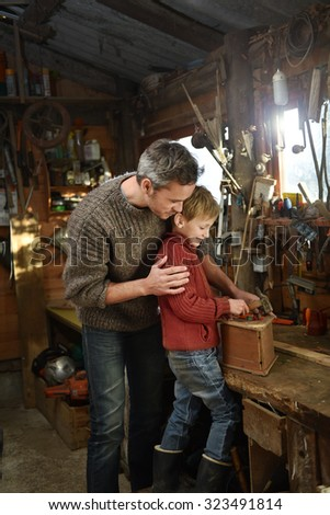 Portrait of a father and his son working together in a traditional wooden workshop. They are having fun while hammering nails on a birdhouse. They are wearing woolen pulls and jeans.