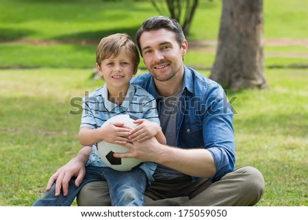 Portrait of a father and son sitting with ball at the park - stock photo