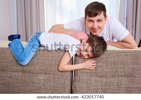 Portrait of a father and son smiling together on the couch in the room. - stock photo