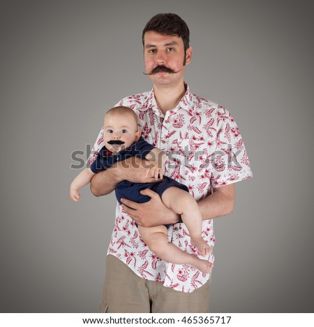 Portrait of a Father with Handlebar mustache holding a baby boy with mustache pacifier, studio isolated on gray background with vignette, square
