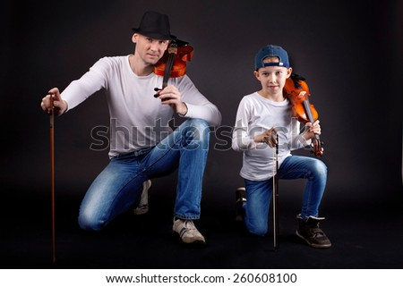 Portrait of a father with his son - posing with his violins. - stock photo