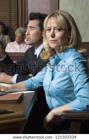 Portrait of a female advocate sitting with colleague and people in the background the court house - stock photo