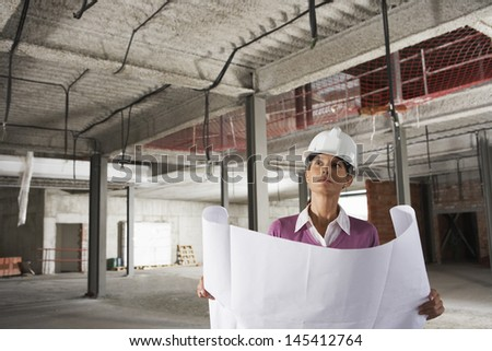 Portrait of a female architect in hardhat with blueprints at construction site - stock photo