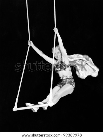 Portrait of a female circus performer performing on a trapeze bar - stock photo