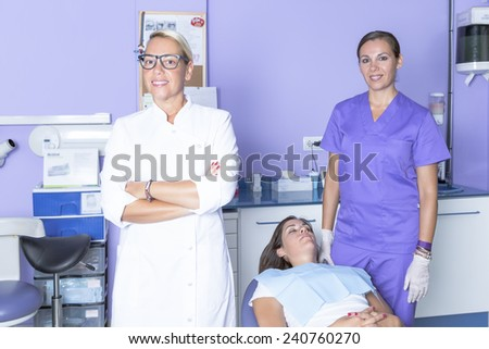 portrait of a female dentist with her assistant at the background and a prepared patient lying on a chair at the dental clinic - stock photo
