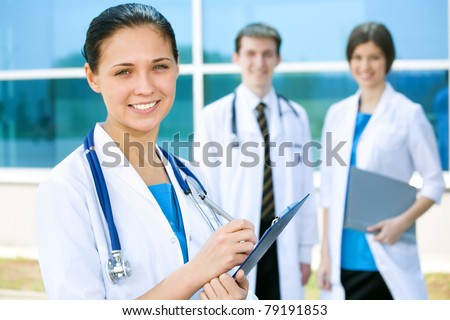 Portrait of a female doctor with two of her co-workers against modern hospital building - stock photo