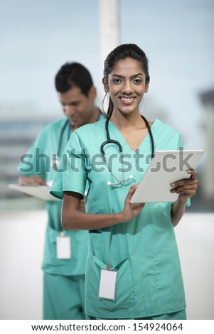 Portrait of a female Indian doctor standing in front of her colleague holding a digital tablet PC