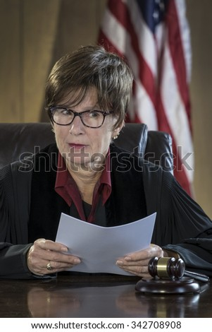 Portrait of a female judge reading a verdict in court - stock photo
