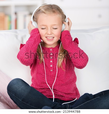 portrait of a female kid enjoying music with closed eyes - stock photo