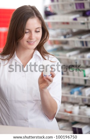 Portrait Of A Female Pharmacist At Pharmacy Reading Information On Medicine. - stock photo