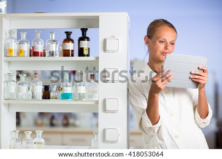 Portrait of a female researcher doing research in a lab (shallow DOF; color toned image) - stock photo