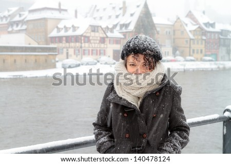 Portrait of a Female Student from Sicily, shot in front of the river Regnitz in Bamberg, shot on a snowy day in Germany in Winter - stock photo