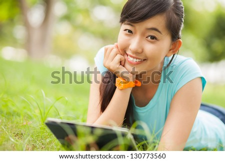 Portrait of a female student lying with gadget outdoors - stock photo