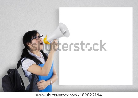 Portrait of a female student shouting via megaphone near to  copy space - stock photo