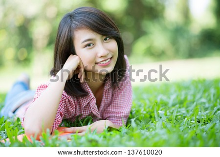 Portrait of a female student smiling and lying on the grass