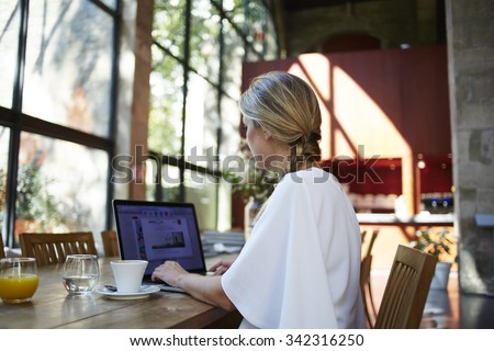 Portrait of a female student using portable laptop computer for preparation to coursework while sitting in university library, young elegant women working on her net-book during coffee brake  - stock photo