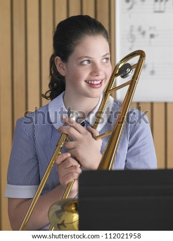 Portrait of a female student with trombone - stock photo