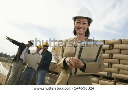 Portrait of a female surveyor with colleagues looking at blueprint on construction site - stock photo