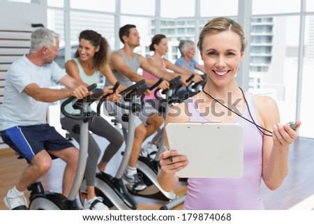 Portrait of a female trainer with people working out at exercise bike class in gym