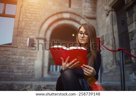Portrait of a female university student reading interesting book on campus, charming teenager sitting outdoors with open book, attractive young girl read absorbing book at beautiful sunny day, flare - stock photo